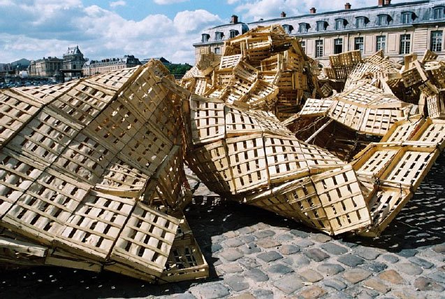 un'opera d'arte in una piazza, fatta di pallet incurvati e collegati tra loro a sembrare un elemento naturale del paesaggio